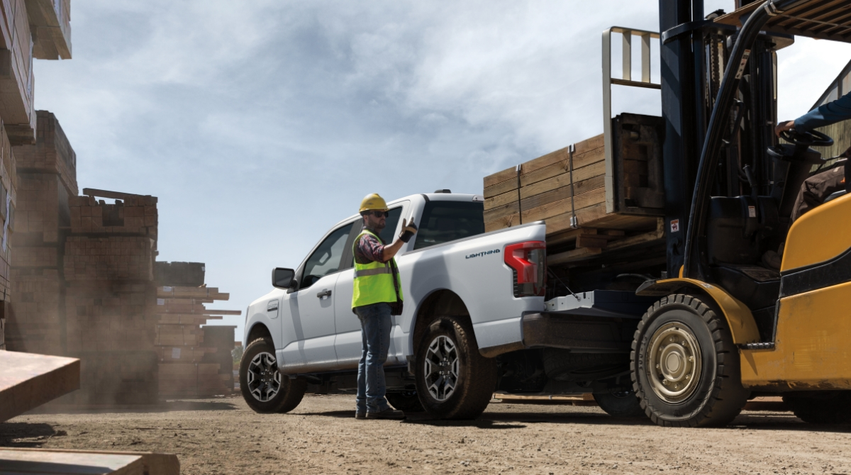 A truck onboarding a large pallet of wood at a commercial site.