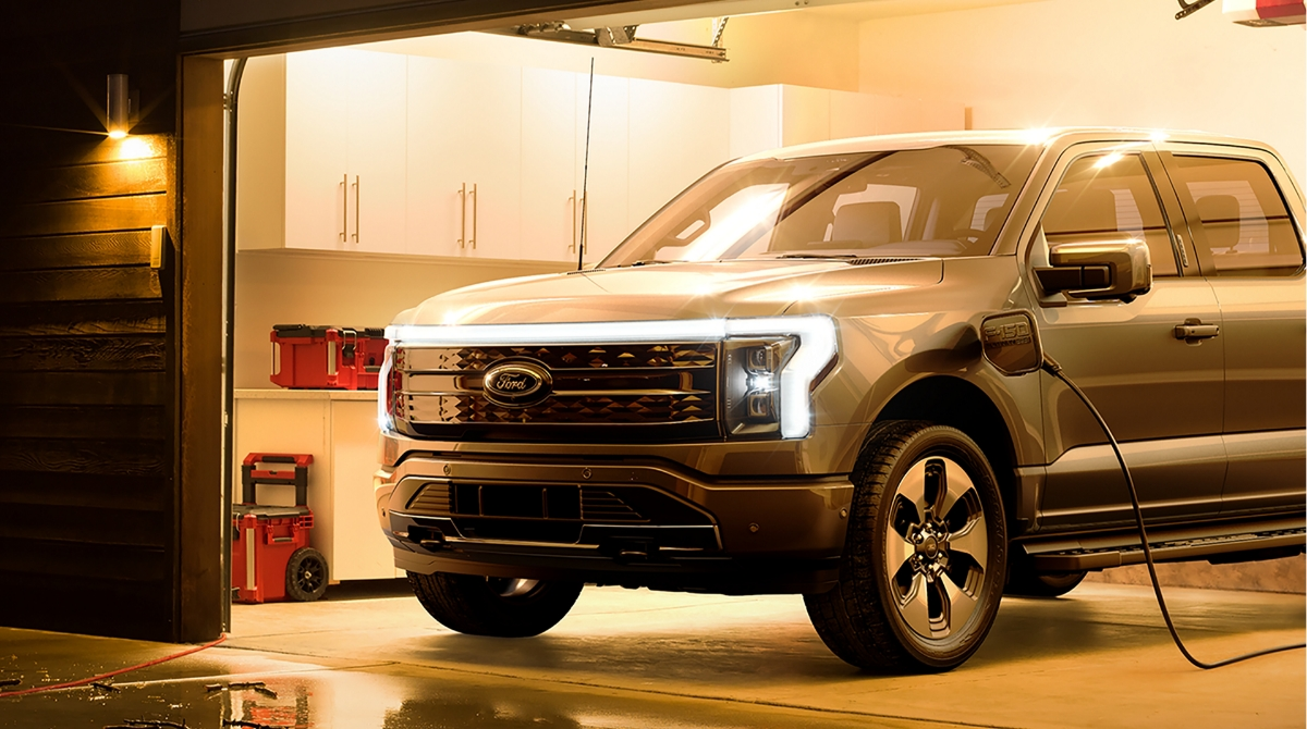 An F-150 Lightning truck being charged in a modern garage.